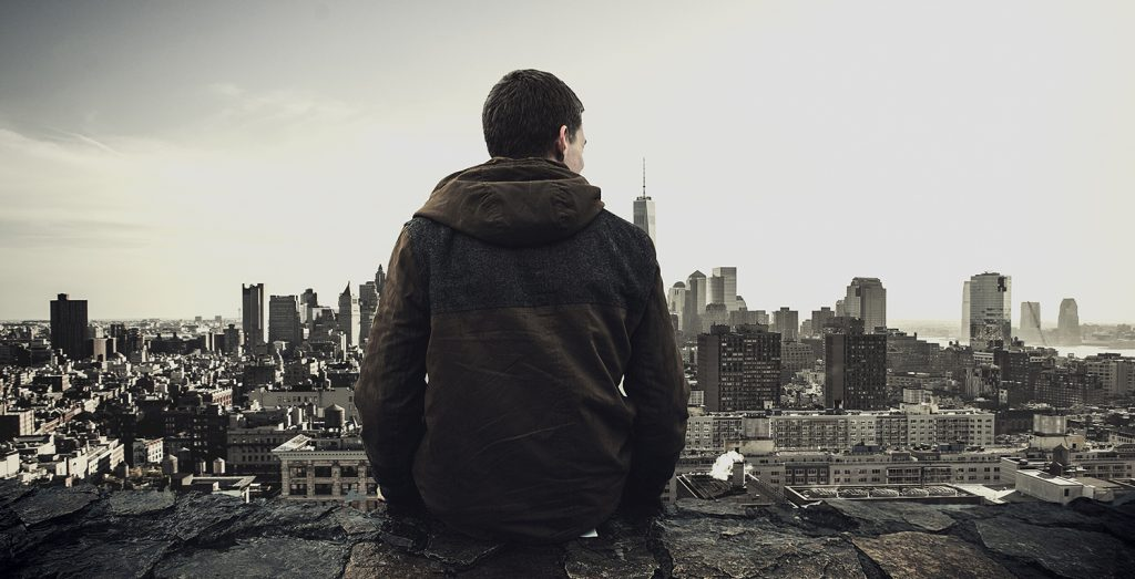Living with depression - picture of back of man sitting on cliff ledge facing big city