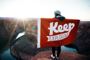 "Radiant Acquiescence - Virtues - Open-Mindedness - Photo of person over cliffs with a banner reading ""Keep Exploring"""