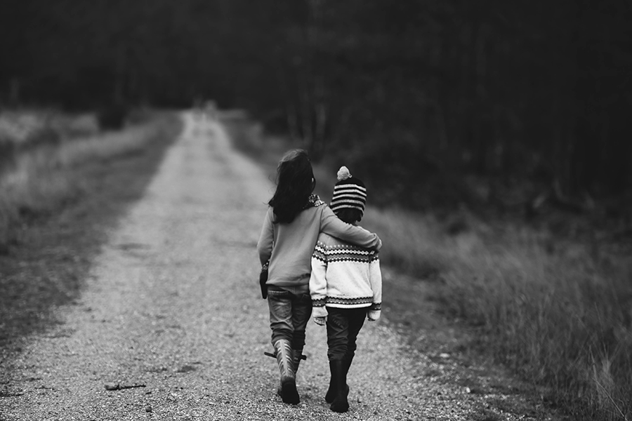 Radiant Acquiescence - Virtues - Open-Mindedness - Photo of the backs of two children walking down a road together with sister's arm around sibling