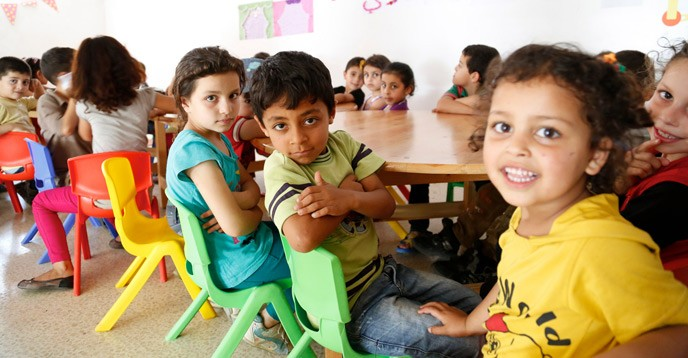 beautiful children sitting at tables in a kindergarten classrooms etting